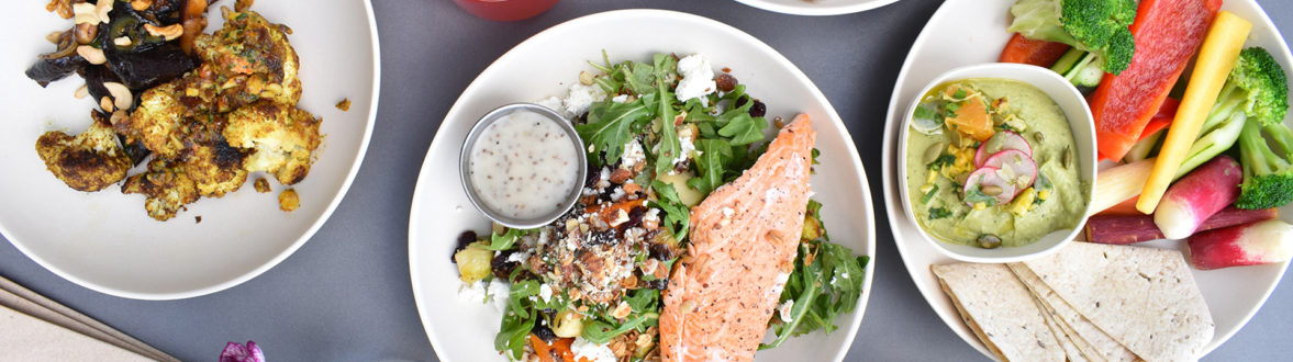 A table with several dishes on it, including salmon salad