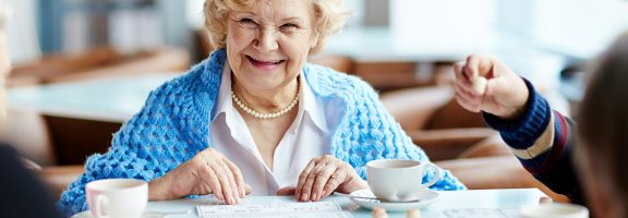 An elderly woman smiling while she plays bingo