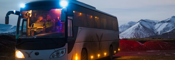 A bus with lights on at dusk